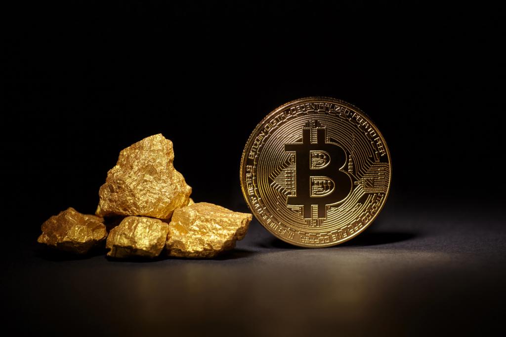 Oro al lado de una moneda con el símbolo de Bitcoin